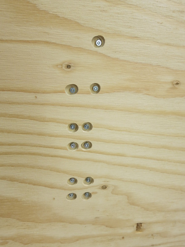 The back of the plywood base, showing the counterbored holes