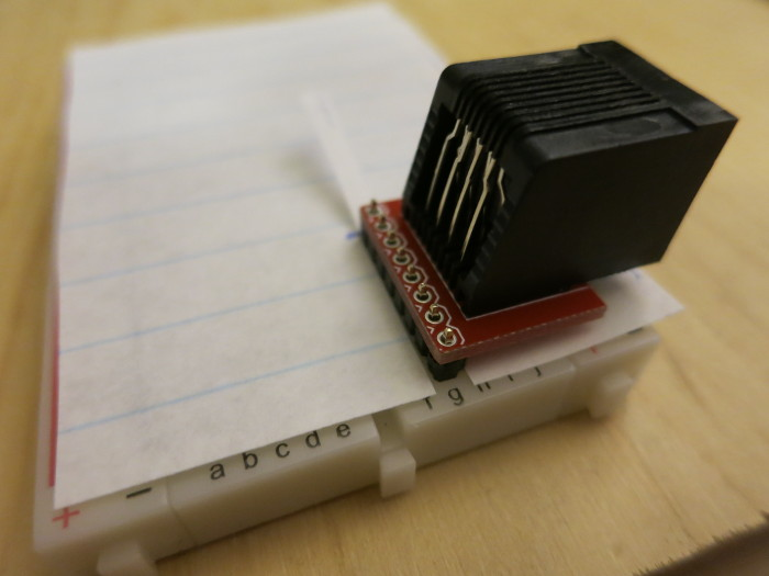 a piece of paper protects the breadboard from solder and flux