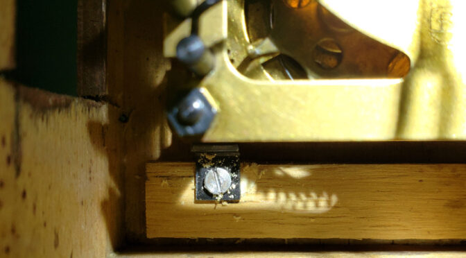 The repaired, stripped screw hole in a cuckoo clock case